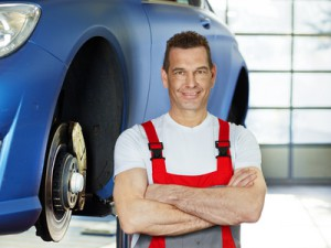 Car mechanic is satisfied with his job in a garage